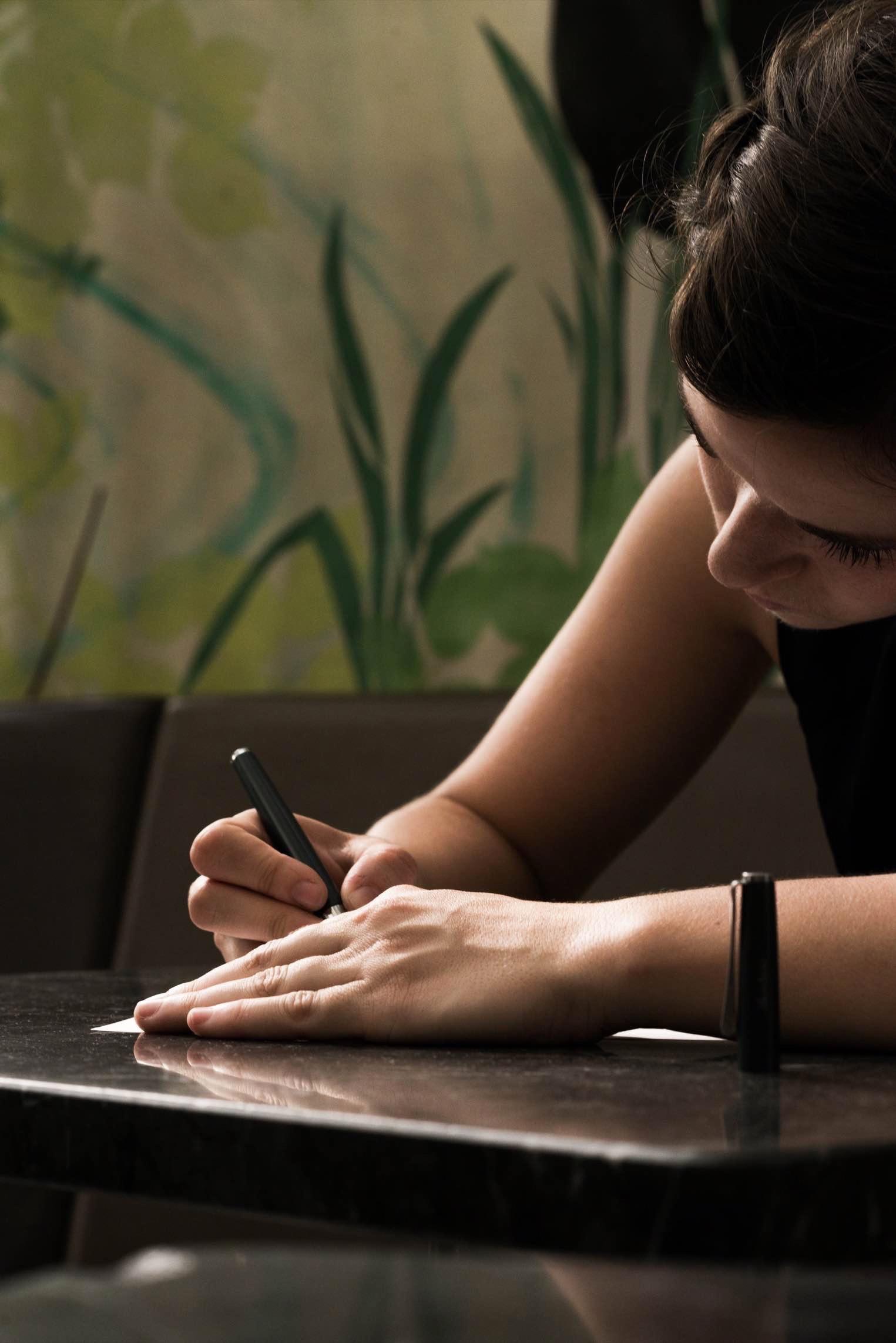 Helena Jordan schreibt auf ein leeres Blatt