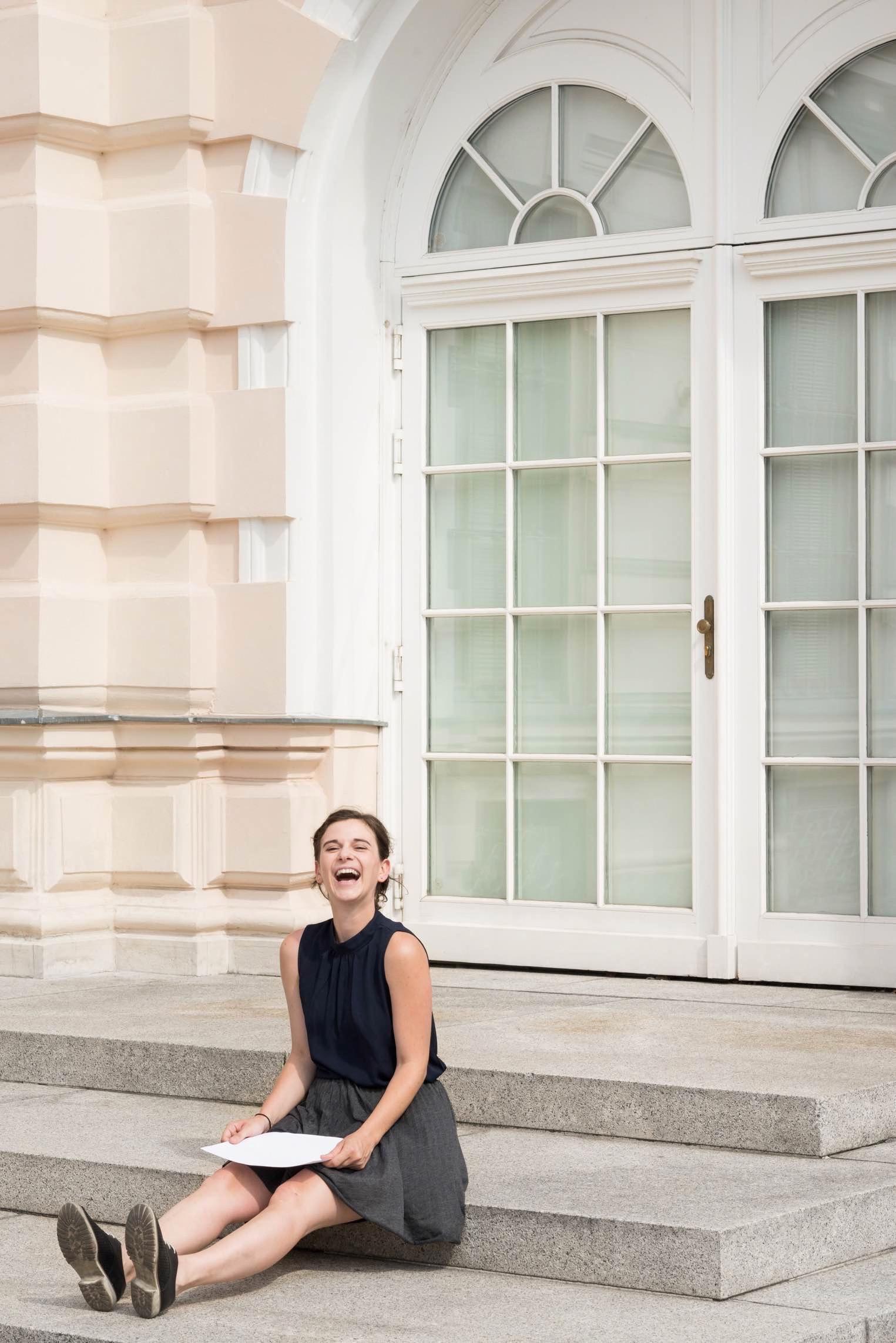Porträt von Helena Jordan; Helena sitzt auf den Stiegen und hält lachend ein weißes Blatt Papier auf ihrem Schoß