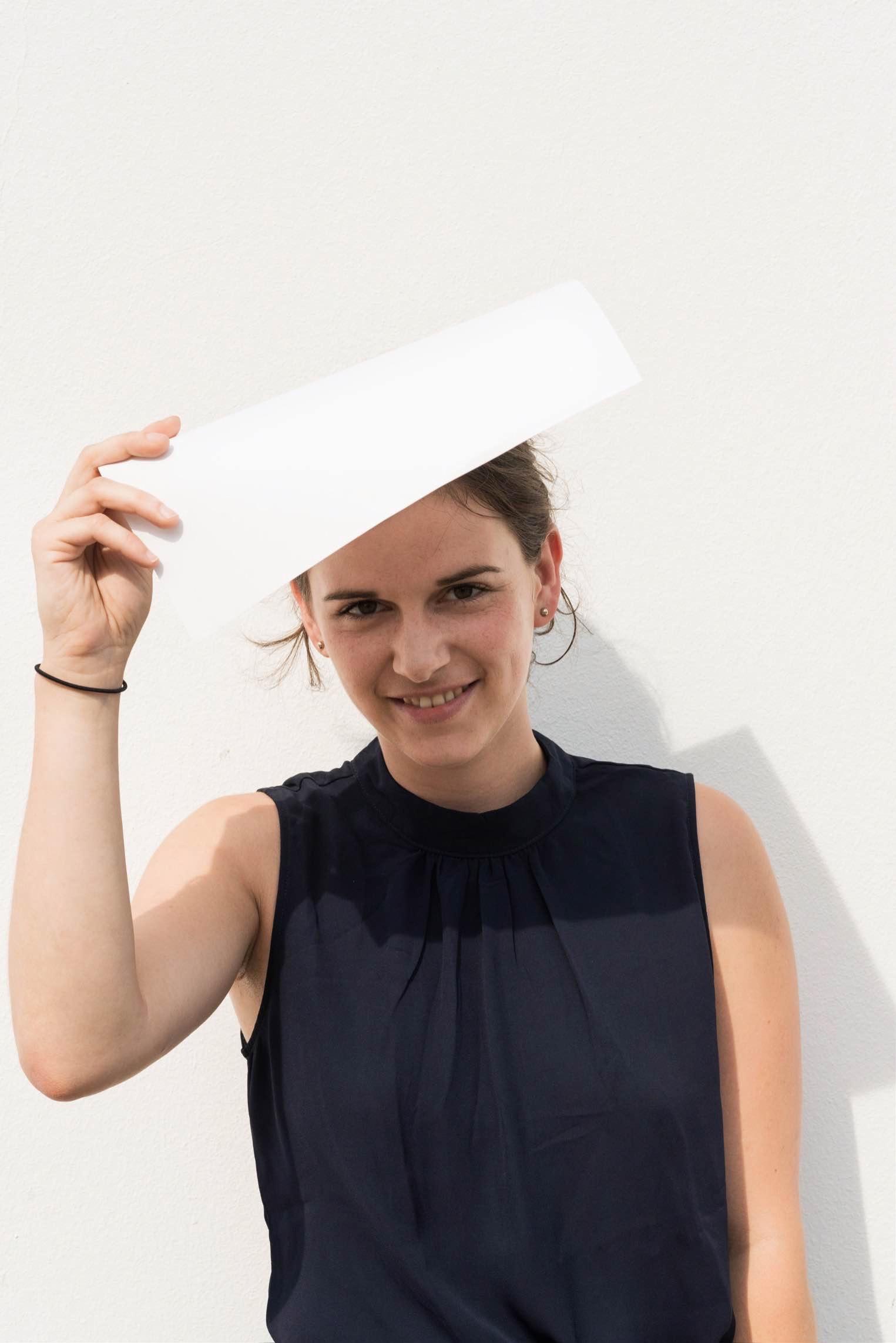 Porträt von Helena Jordan; Helena lacht und hält ein weißes Papier über ihre Stirn als Sonnenschutz