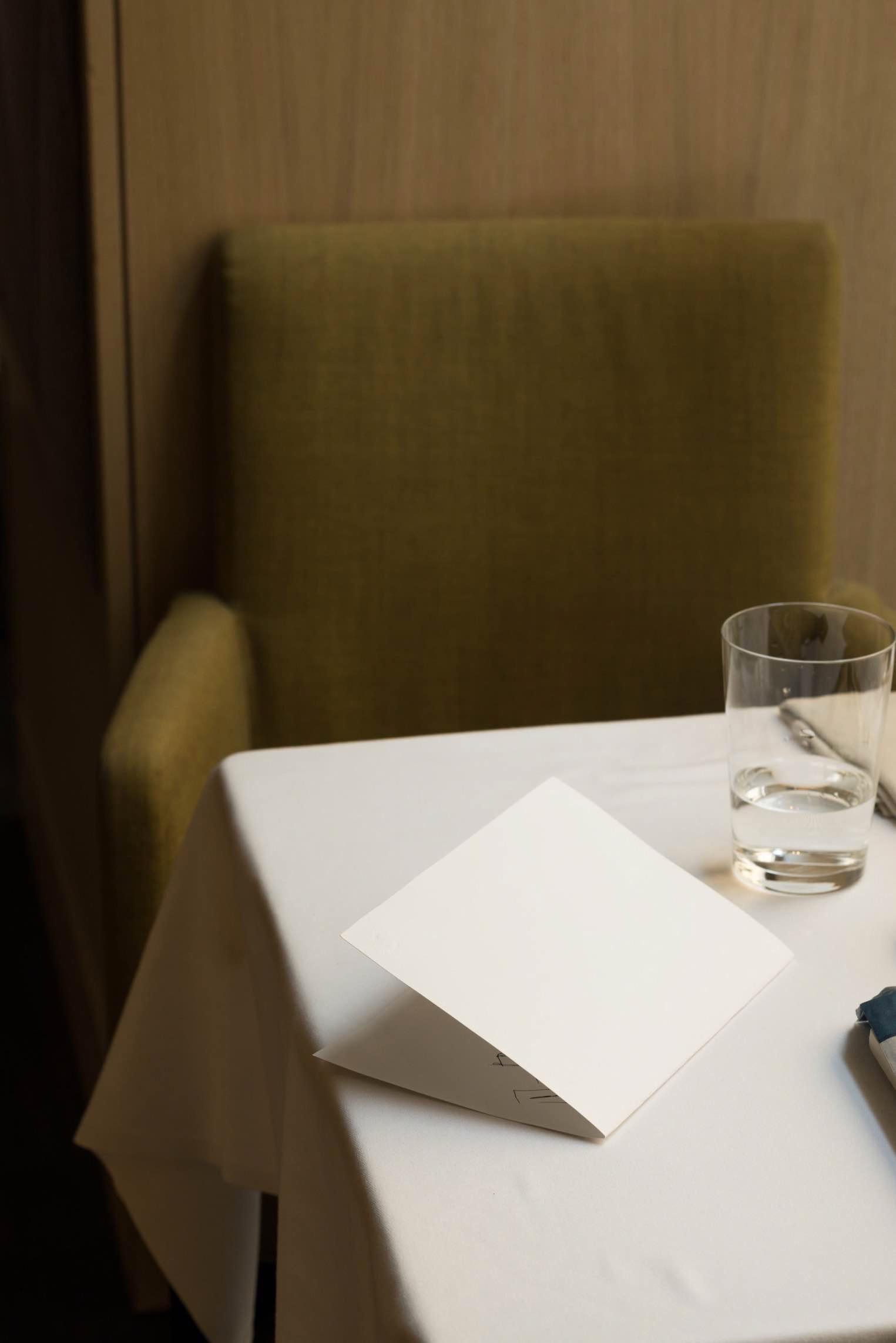 Kaffeehaustisch mit gefaltetem weißem Papier und Glas